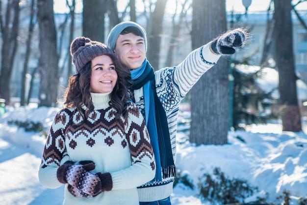 愛のカップルは冬の公園で抱擁します。 Premium写真
