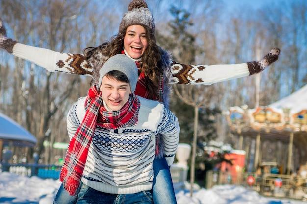 女性は、ウィンターパークで彼氏の背中に乗る。ガールフレンドピギーバックを与える男 Premium写真