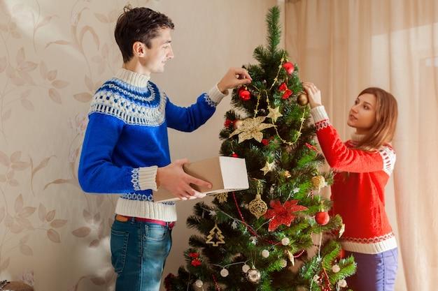 冬のセーターを着て、自宅でクリスマスツリーを飾る愛のカップル。新年の準備 Premium写真
