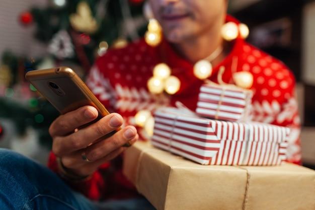 新年を買う男がスマートフォンを使用してプレゼント Premium写真