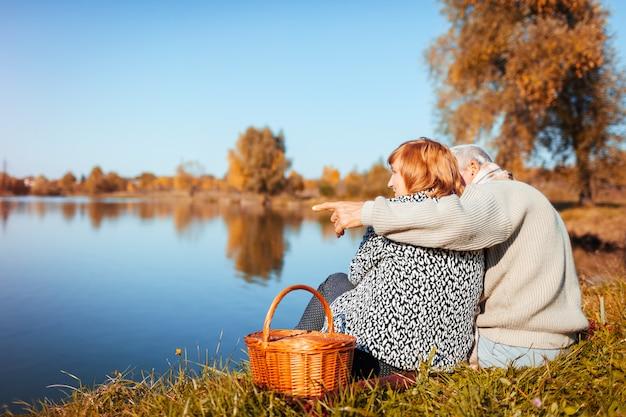 秋の湖でピクニックをしている年配のカップル Premium写真