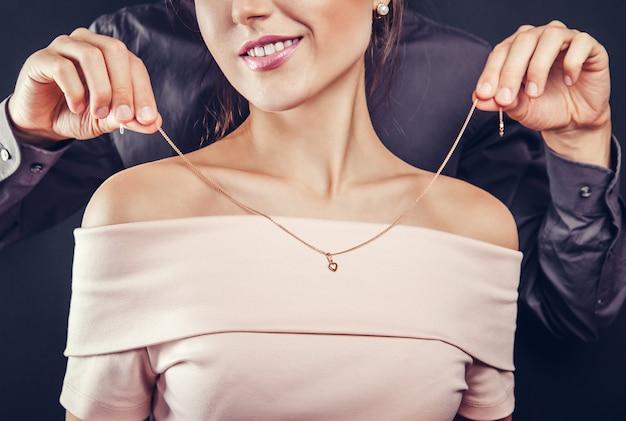 金色のネックレスを試着するために彼のガールフレンドを助ける男。バレンタインデーのギフト。 Premium写真