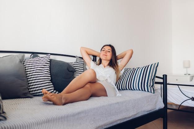 自宅のソファに横たわっているリビングルームでリラックスした女性。週末の朝。自由時間を楽しむ Premium写真