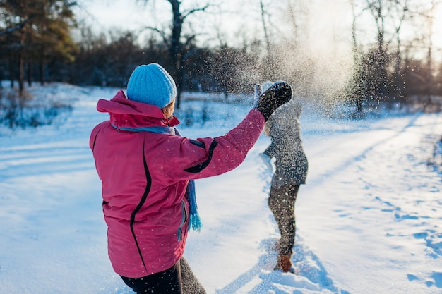Снежки играют в зимнем лесу. семья мать и дочь весело бросать снег на открытом воздухе Premium Фотографии