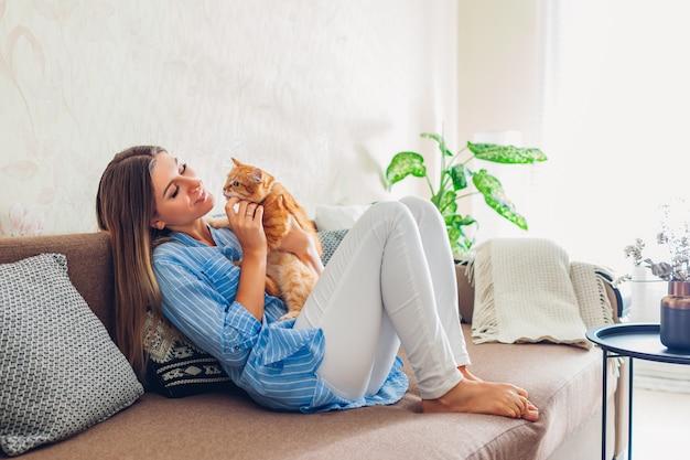 Молодая женщина сидит и отдыхает на диване в гостиной и обниматься, играя с домашним животным Premium Фотографии
