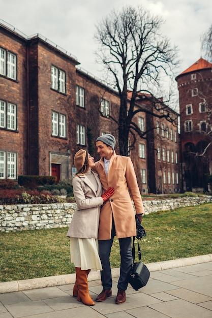 ポーランド、クラクフのヴァヴェル城の建築を楽しんでハグを歩くスタイリッシュな観光客のカップル。 Premium写真
