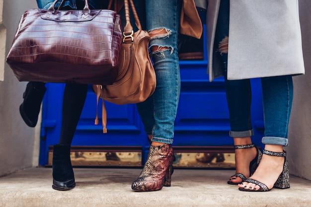 Три женщины носить стильную обувь и аксессуары на открытом воздухе. концепция красоты моды. дамы, держащие женские сумки Premium Фотографии