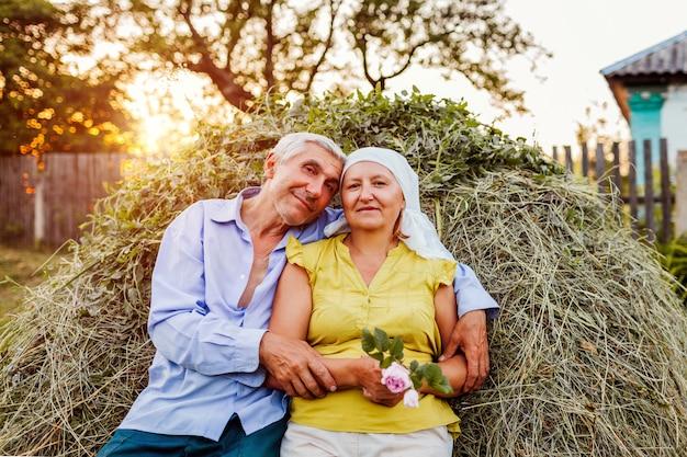 干し草の山の上に座って、田舎で夕暮れ時にリラックスした農家の家族カップル。 Premium写真
