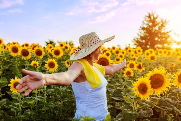 年配の女性が咲くひまわり畑を歩いて自由と感心の景色。夏休み Premium写真