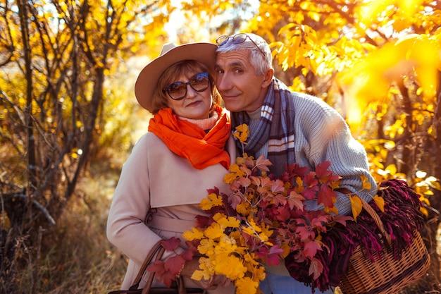 秋の森を歩く年配のカップル。 Premium写真