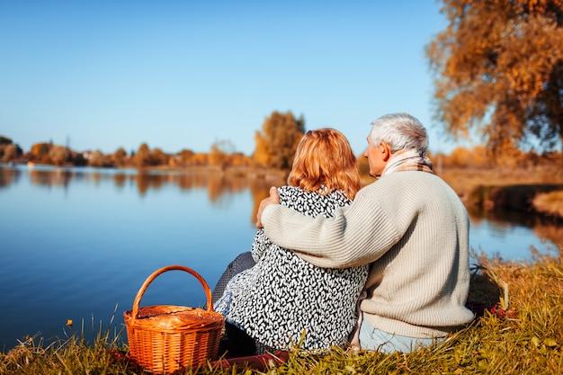 秋の湖でピクニックを持っている年配のカップル。 Premium写真