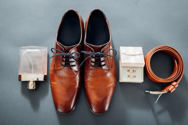 Коричневые кожаные туфли, пояс, духи и золотые кольца. Premium Фотографии