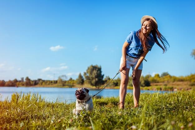 川のそばに座ってパグ犬。マスターの命令を待っている幸せな子犬。犬と女が屋外で低温 Premium写真