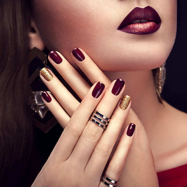 Красивая женщина с идеальным макияжем и бордовым и золотым маникюром Premium Фотографии