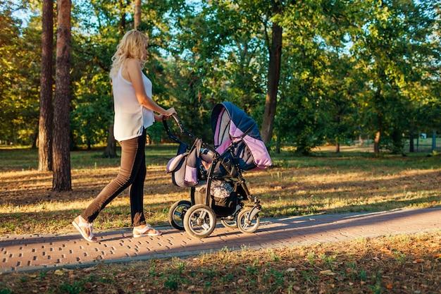 Молодая мать гуляя в парк лета с детской дорожной коляской. Premium Фотографии