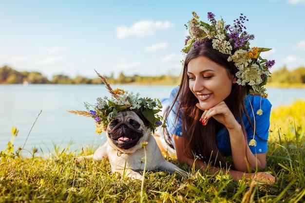 パグ犬とその主人は花の花輪を身に着けている川で身も凍る。 Premium写真