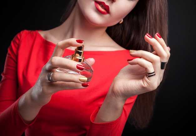 黒の背景に彼女の手首に香水を適用する女性 Premium写真