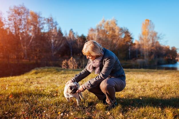 川で秋の公園でパグ犬を歩きます。ペットと遊んで、親友と楽しんで幸せな女。 Premium写真