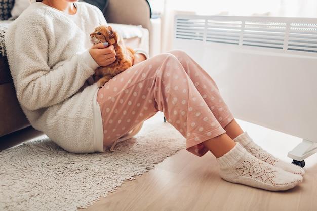 冬に家でヒーターを使用します。女性は猫と体を温暖化します。暖房シーズン。 Premium写真