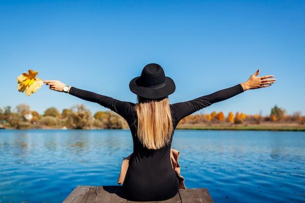 Осенние флюиды. молодая женщина ослабляя рекой с оружиями подняла сидеть на пристани. Premium Фотографии