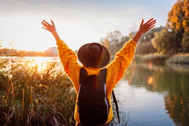 夕暮れ時の秋の川でリラックスしたバックパックを持つ旅行者。若い女性は、自由で幸せな感じの腕を上げた Premium写真
