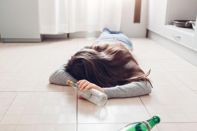 女性のアルコール中毒。パーティー開催ボトル後キッチンの床で寝ている若い女性 Premium写真