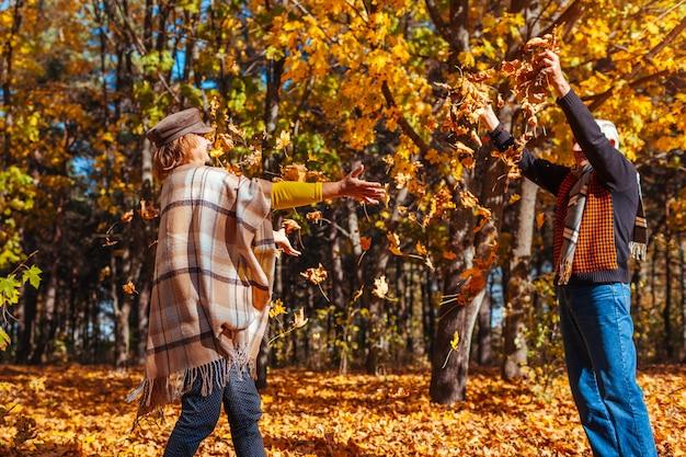秋のシーズン。秋の森で葉を投げるカップル Premium写真