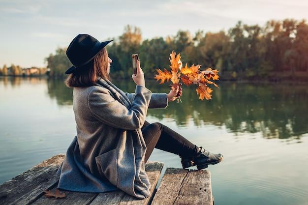 秋のシーズン。川の桟橋でスマートフォンを使用して葉と枝の写真を撮る女性 Premium写真