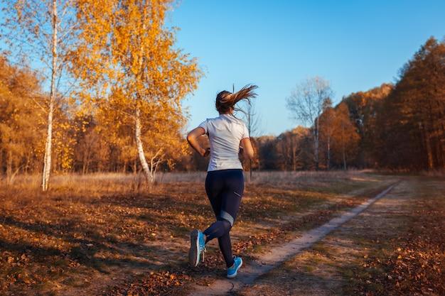 ランナーのトレーニングと秋の公園、日没で走っている女性、アクティブな健康的なライフスタイルで運動 Premium写真