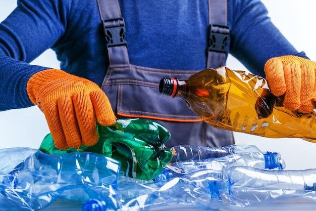 リサイクルのためにプラスチックのゴミを分別する労働者。 Premium写真