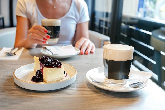 Женщина ест торт и кофе в кафетерии. Premium Фотографии