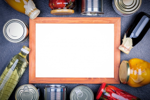 Различные консервированные овощи, мясо, рыба и фрукты в олова и стекла с доской. Premium Фотографии