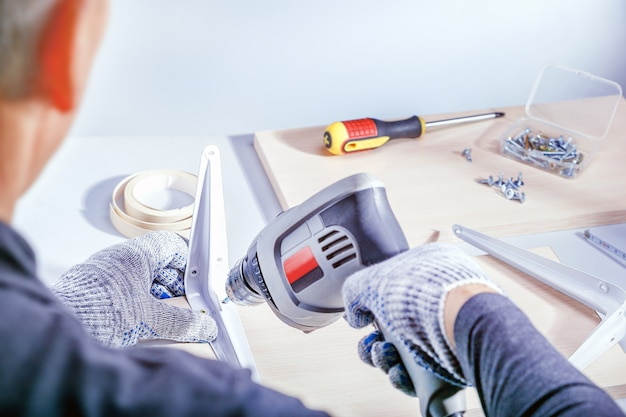 大工のワークショップで家具を作る男性の手のクローズアップの肖像画。家具の組み立て Premium写真