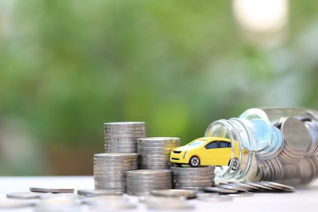 ガラス瓶の中のコインお金のスタック上のミニチュア黄色の車モデル Premium写真