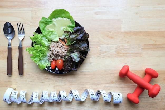 ダンベルと暗い木の上の測定テープと野菜のサラダのトップビュー Premium写真