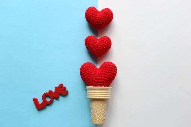Красное вязаное сердце ручной работы в вафельном стаканчике на желто-розовом фоне на день святого валентина Premium Фотографии