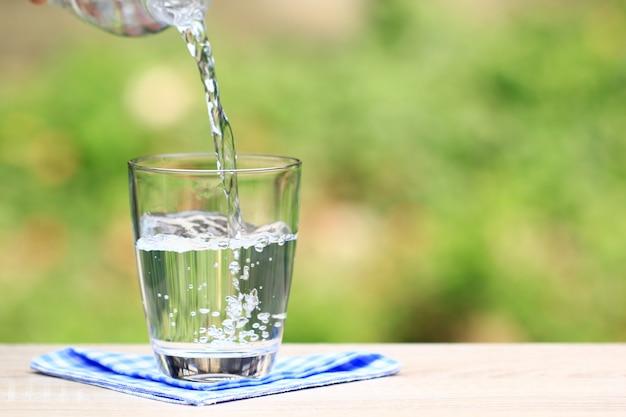 テーブルの自然に水の入ったグラス Premium写真