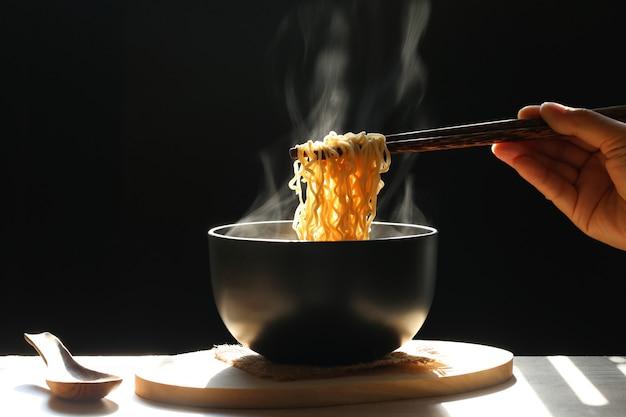 Женщина рука палочками лапши быстрого приготовления в чашке с дымом темнеет, натриевая диета с высоким риском почечной недостаточности, здоровое питание приготов Premium Фотографии