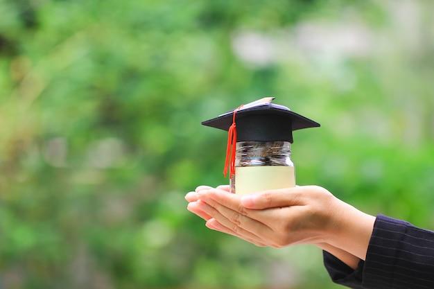 卒業生の帽子、教育概念のためのお金を節約とガラス瓶にコインのお金を持つ女性の手 Premium写真
