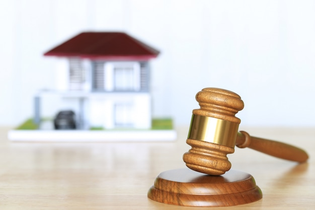 Молоток деревянный и модельный дом на фоне из массива Premium Фотографии