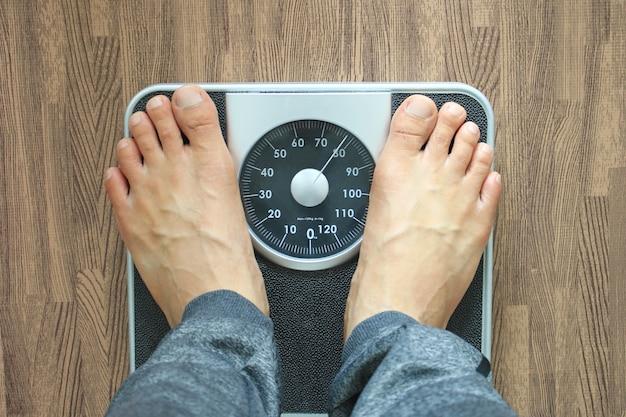 チェック体重、ダイエットの概念の体重計の男性 Premium写真