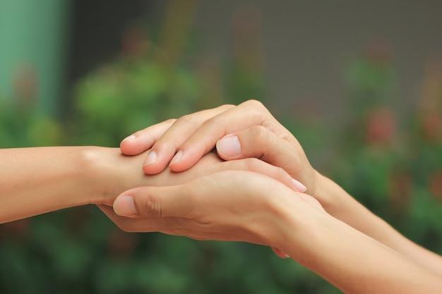 男と女の愛のロマンチックなカップルの手を繋いでいます。 Premium写真