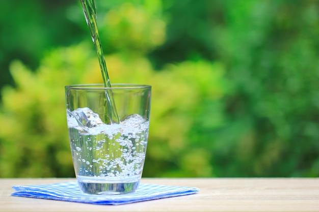Крупным планом стакан воды на столе Premium Фотографии