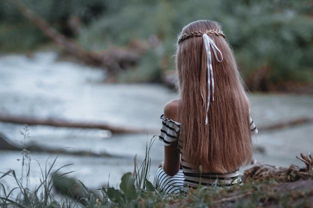 湖の素晴らしい景色を見て、長い髪の少女。 Premium写真