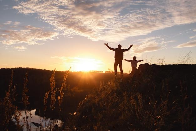 自由な男と自由を楽しんで、夕暮れ時に幸せを感じている子供のシルエット。 Premium写真