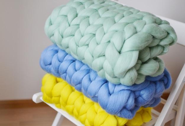 ジャイアントピンクミントイエローブルーブランケットチェック柄メリノウールニットホワイト木製スツール椅子ホームインテリア Premium写真