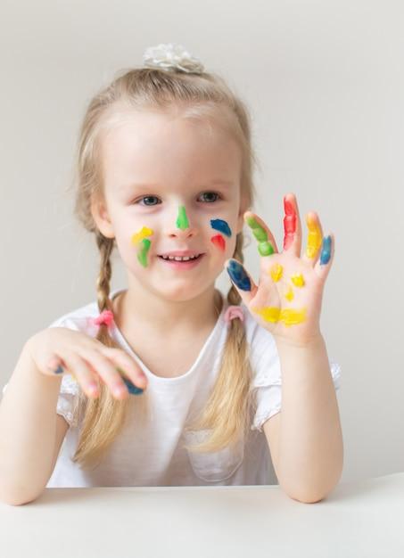 カラフルな手で白人の少女絵画家で早期塗装学校の就学前の開発の子供のゲームの準備 Premium写真