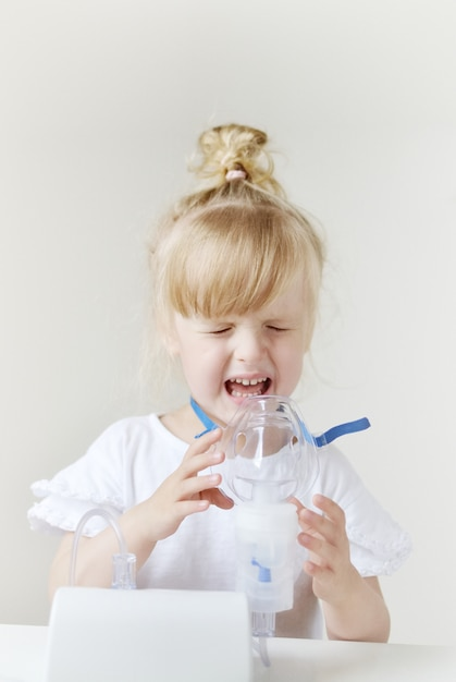 テーブル、屋内、病気の子供の自宅吸入器でネブライザーで吸入を行う吸入用マスクの少女 Premium写真