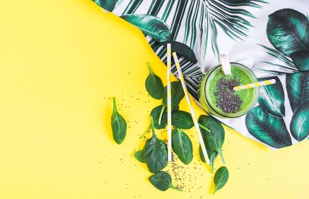 チア種子、健康食品のコンセプト、朝食、黄色の背景が付いている瓶に緑のほうれん草のスムージー Premium写真