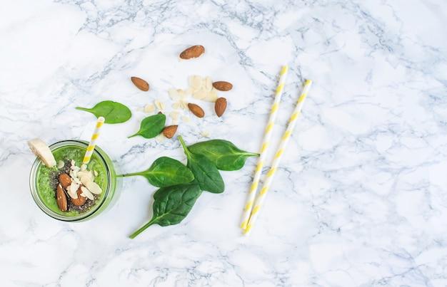 チア種子、アーモンドナッツ、健康食品のコンセプトが付いている瓶に緑のほうれん草のスムージー Premium写真